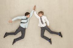 Business pojat antaa high five vastaan beige tausta Kuvituskuvat