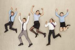 Germany, Berlin, Business kids flying against beige background - stock photo