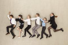 Stock Photo of Business kids running against beige background