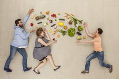 Men and woman with food against beige background Stock Photos