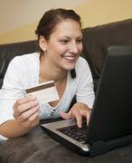 Germany, Brandenburg, Young woman shopping online from home with laptop and Stock Photos