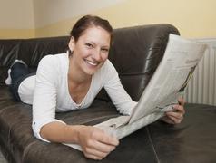 Germany, Brandenburg, Young woman reading newspaper Stock Photos