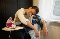 Germany, Brandenburg, Exhausted young woman leaning on ironing board - stock photo