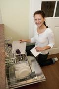 Germany, Brandenburg, Young woman loading dishwasher, smiling, portrait Stock Photos