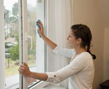 Stock Photo of Germany, Brandenburg, Young woman cleaning window