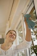 Germany, Brandenburg, Young woman cleaning window - stock photo