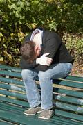 Stock Photo of Germany, Berlin, Depressed man sitting on park bench