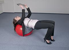 Germany, Berlin, Businesswoman bending over exercise ball with digital tablet - stock photo