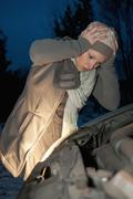 Germany, Brandenburg, Shocked young woman with car breaks down at night Stock Photos
