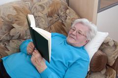 Germany, Berlin, Senior woman reading book Stock Photos