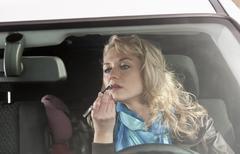 Germany, Brandenburg, Woman applying lipstick in car Stock Photos