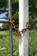padlock with an iron chain at fence - stock photo