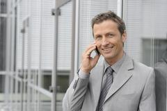 Stock Photo of Europe, Germany, Bavaria, Businessman talking on mobile, smiling, portrait