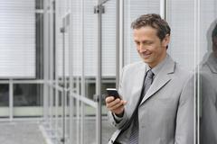 Europe, Germany, Bavaria, Businessman using mobile, smiling - stock photo