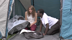 Attractive teenage couple putting up a tent (clip 5) Stock Footage