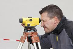 Mature man looking through theodolite Stock Photos
