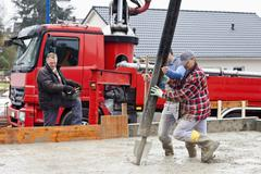 Europe, Germany, Rhineland-Palatinate, Construction workers filling concrete for Stock Photos