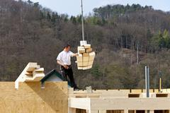 Stock Photo of Europe, Germany, Rhineland Palantinate, Man installing and fixing wooden walls