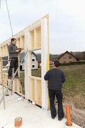 Stock Photo of Europe, Germany, Rhineland Palantinate, Men installing and fixing wooden walls