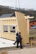 Europe, Germany, Rhineland Palantinate, Men installing and fixing wooden walls - stock photo