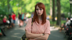 Young Caucasian woman walking in a park sad face - stock footage