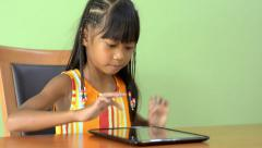Young Asian Girl Playing With an iPad  At The Table Stock Footage