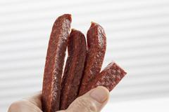 Stock Photo of Human hand holding spicy sausage, close up