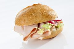 Stock Photo of Sandwich of bread roll with mortadella and poultry on white background, close up