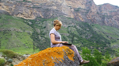 A woman is sitting on a huge rock and prints on the laptop Stock Footage