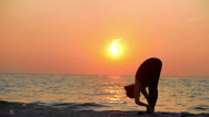 A young woman with a slender figure is engaged in gymnastics at sea at sunrise Stock Footage