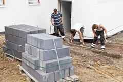 Stock Photo of Germany, Rhineland Palatinate, Workers laying paving stones in soil