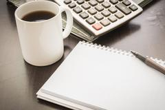 Coffee cup, document file , pen , calculator , notepad  on wooden table Stock Photos