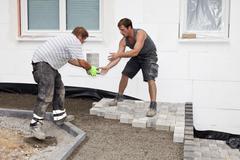 Stock Photo of Germany, Rhineland Palatinate, Workers assembling paving stones