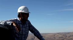 Man Views the Landscape Atop a Wind Turbine - stock footage