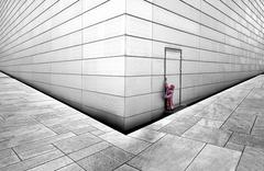 Norway, Oslo, Girl trying to open door of opera house - stock photo