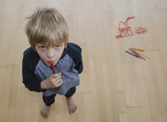 Austria, Portrait of little boy holding coloured pencil - stock photo