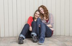 Portrait of young women leaning against planked wall, smiling Stock Photos
