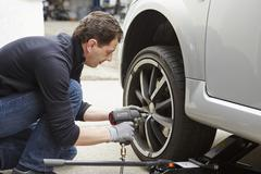 Germany, Bavaria, Kaufbeuren, Mature man changing car tire Stock Photos