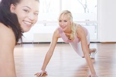 Stock Photo of Germany, Brandenburg, Instructor and woman doing exercise in gym, smiling