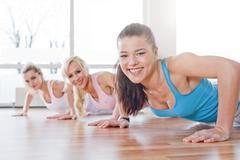 Germany, Brandenburg, Women doing exercise in gym, smiling - stock photo