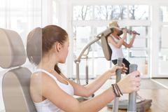 Stock Photo of Germany, Brandenburg, Young women exercising in gym
