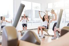 Germany, Brandenburg, Instructor with women exercising in gym - stock photo