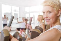 Germany, Brandenburg, Women exercising in gym, smiling Stock Photos