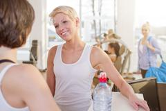 Germany, Brandenburg, Women refreshing after workout in gym, smiling Stock Photos