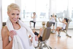 Germany, Brandenburg, Female instructor at gym, smiling, portrait Stock Photos