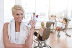 Germany, Brandenburg, Woman holding water bottle, smiling, portrait Stock Photos