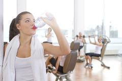 Germany, Brandenburg, Woman drinking water at gym - stock photo