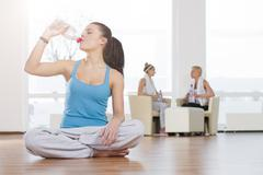 Stock Photo of Germany, Brandenburg, Woman drinking water at gym