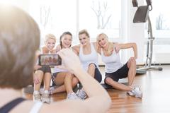 Stock Photo of Germany, Brandenburg, Woman taking photo of women in gym, smiling