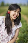 Germany, Bavaria, Young Japanese woman with strawberry earrings - stock photo